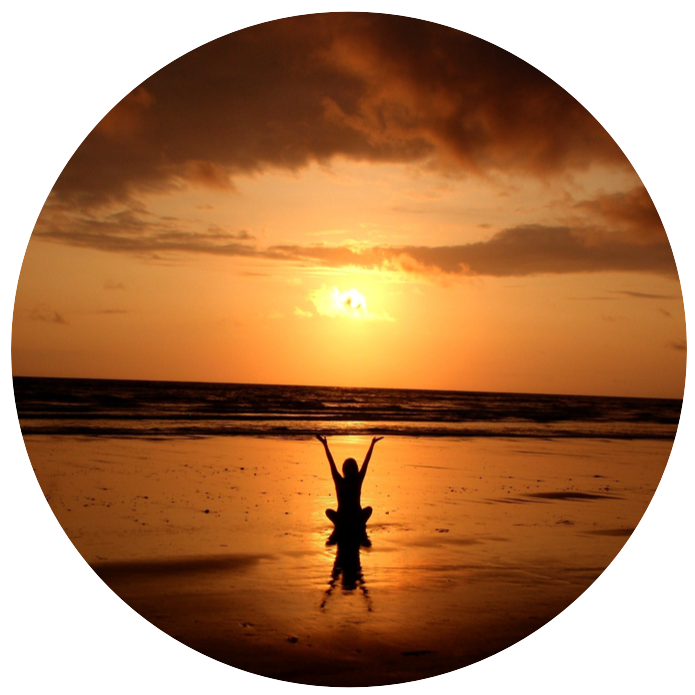 Woman sitting from behind on beach, watching sunset, with hands spread above head - symbolizes healing, connection to inner self, and freedom.